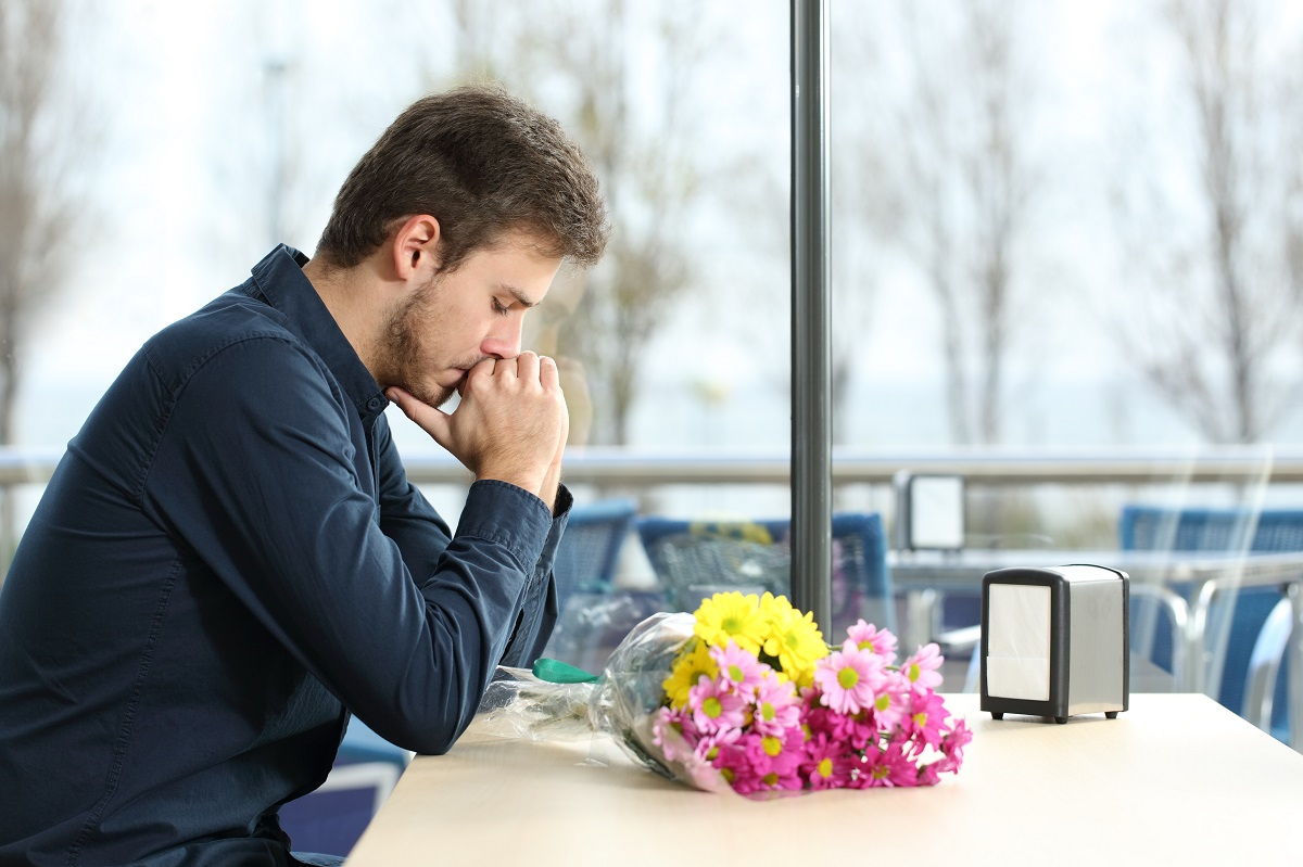 Sad man with flowers on table