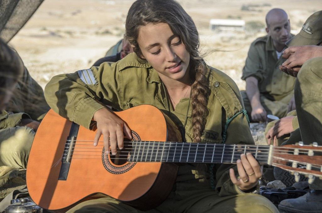 woman soldier playing guitar