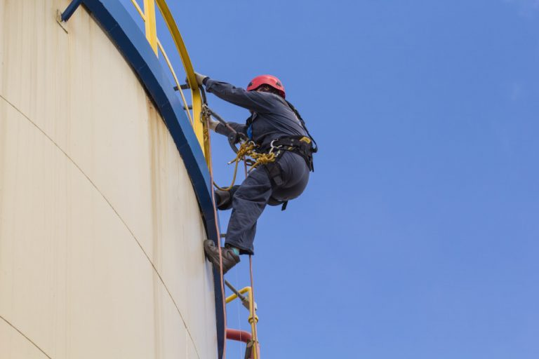 man on top of oil container