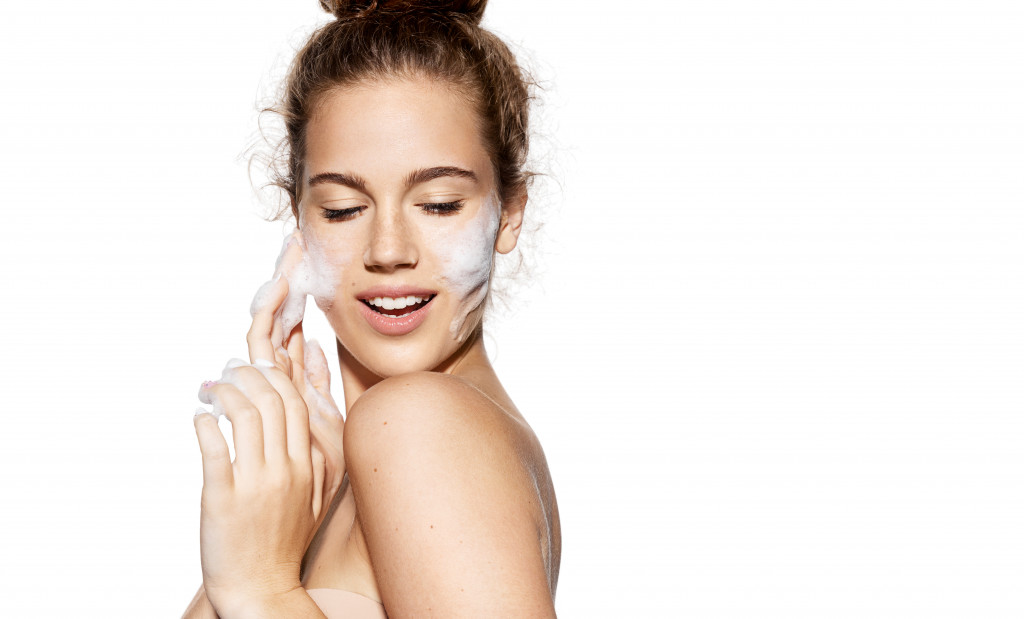 woman putting on skin care products